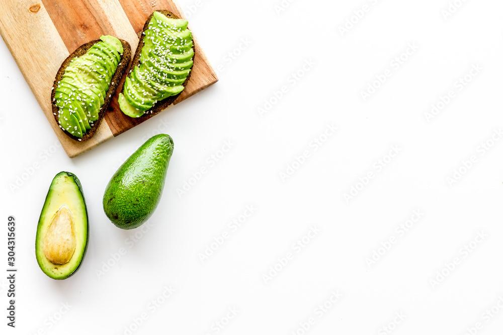 Fototapeta Healthy food. Avocado toast on white background top view frame copy space