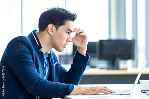 Obraz na plátně  Stressed businessman worked with laptop computer and having a headache after business losses In the office room background