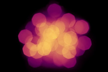 Defocused Violet Orange Spot Of Light On A Black Background Blurred In Beautiful Bokeh. Abstract Trendy Holiday Background
