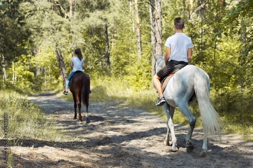 Group of teenagers on horseback riding in summer park Canvas Print