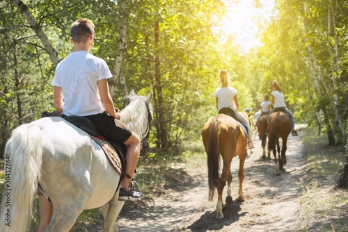 Group of teenagers on horseback riding in summer park Fototapeta