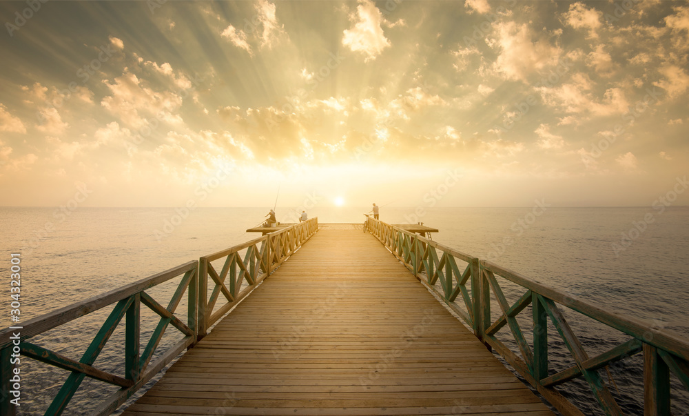 Fototapeta Wooden pier on sea at morning sunrise
