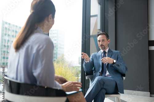 Obraz na plátne  Businessman wearing elegant suit speaking with famous journalist