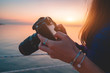 Woman photographer holds dslr camera during taking photos sea at sunset