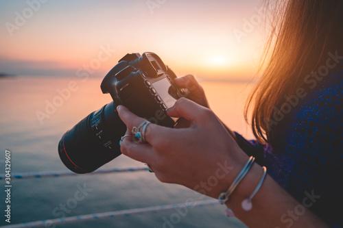 Obraz Woman photographer holds dslr camera during taking photos sea at sunset - fototapety do salonu