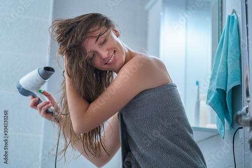 Fototapeta Happy attractive caucasian joyful brunette woman in bath towel dries hair with hair dryer in bathroom after shower at home. obraz