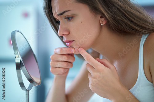 Upset stressed sad acne woman with problem skin squeezes pimple at home in front Canvas Print