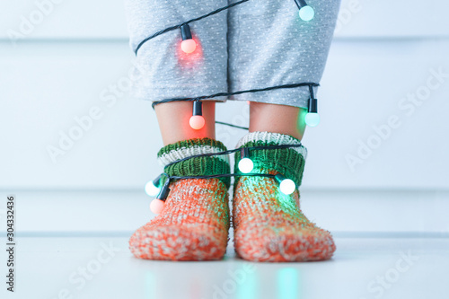 Obraz Female legs in warm knitted soft cozy christmas socks and garland with illuminated lights in wintertime at home. - fototapety do salonu