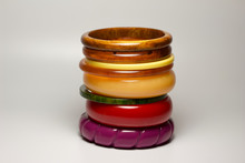 Close Up View Of Vintage Bakelite Bangle Bracelets In Varying Colors And Widths On White Background