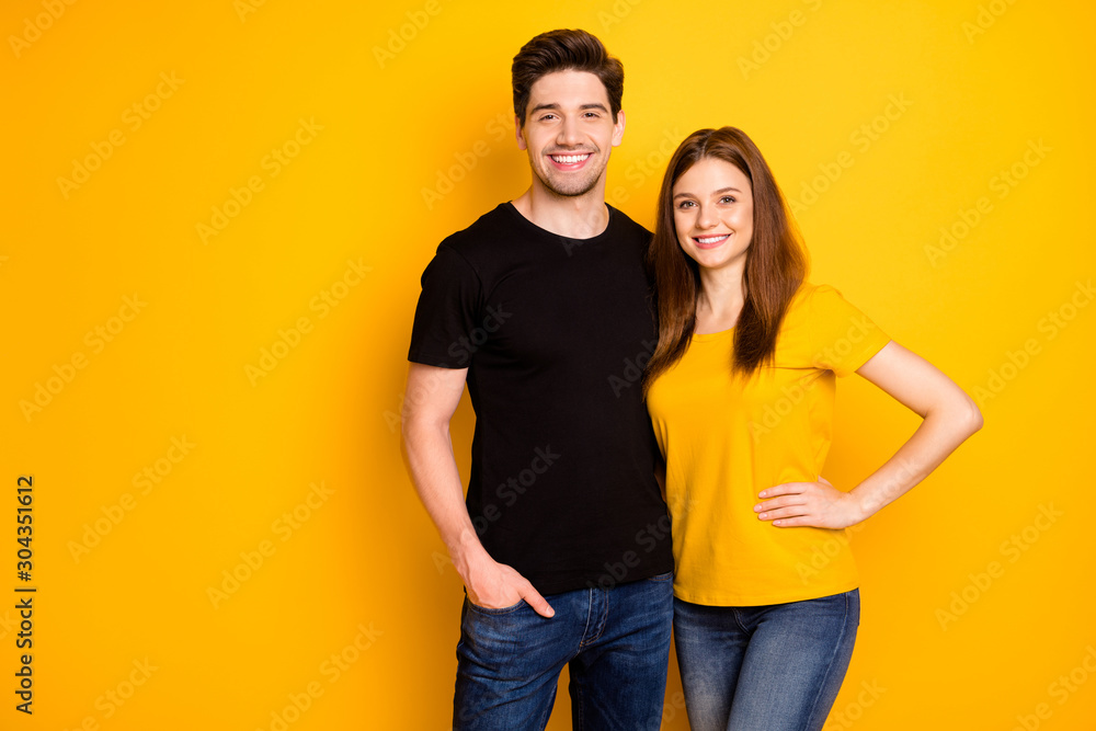 Fototapeta Photo of cheerful positive nice cute pretty couple hugging with man holding hand in jeans denim pocket smiling toothily isolated over vivid color background