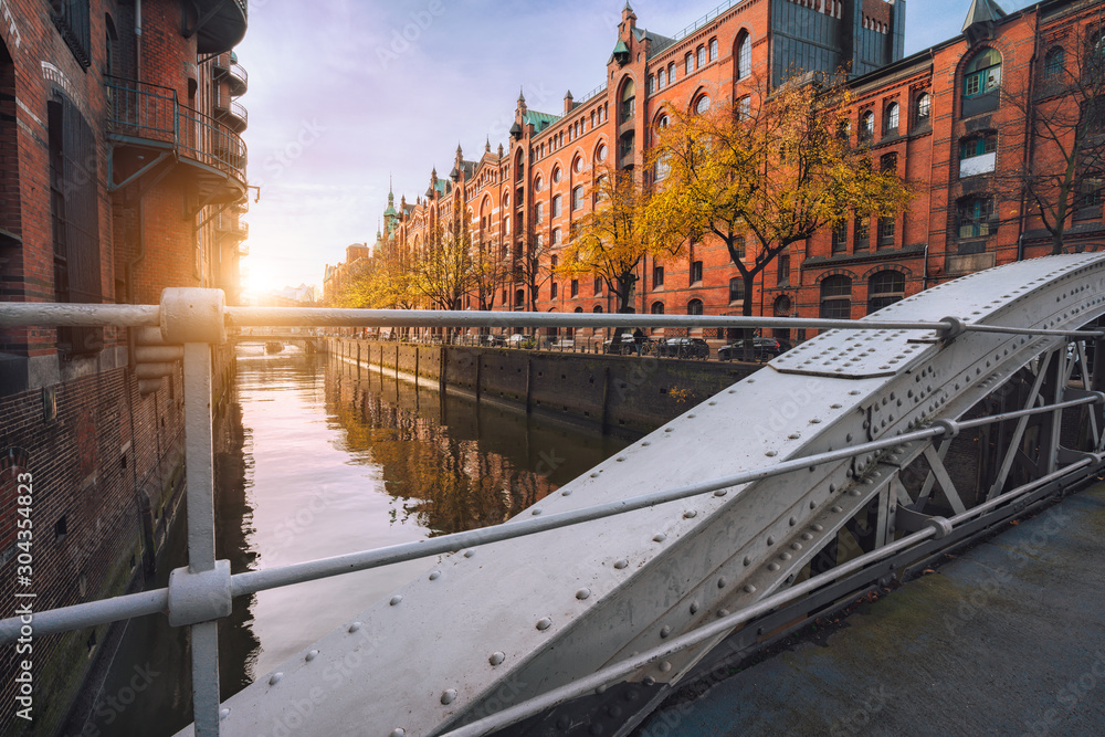 Fototapety, obrazy: Arch bridge over canals in the Speicherstadt of Hamburg, Germany, Europe. Historical red brick building lit by warm soft golden sunset light