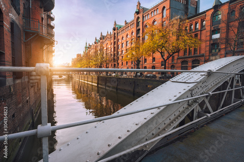 Arch bridge over canals in the Speicherstadt of Hamburg, Germany, Europe. Historical red brick building lit by warm soft golden sunset light - 304354823