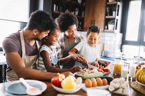 Fototapeta Happy african american family preparing healthy food together in kitchen obraz