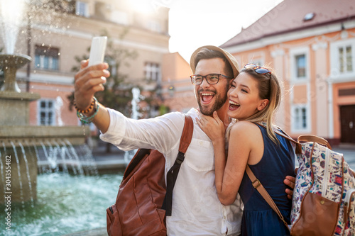 Obraz Happy tourist couple in love having fun, travel, smiling on vacation - fototapety do salonu
