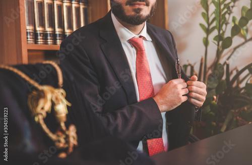 Photo Giovane avvocato nello studio che prende la penna stilografica dalla tasca inter