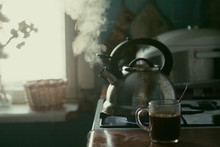 Kitchen. A Metal Kettle Boils On The Stove. A Cup Of Coffee. Window. Brown Set.