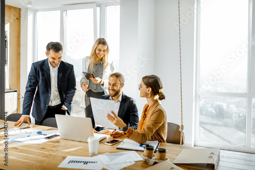 Group of a young office employees dressed casually in the suits having some office work at the large meeting table in the bright sunny room