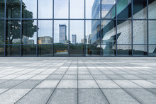 Buildings And Clean Road Reflected On The Glass Wall