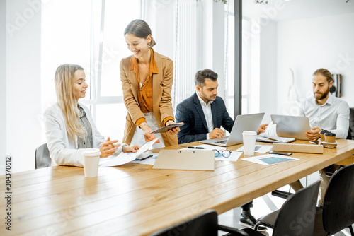 Fototapety, obrazy: Group of a young office employees dressed casually in the suits having some office work at the meeting table in the bright office