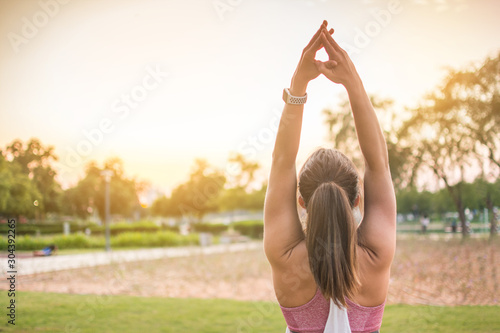 Back view of sporty woman practicing yoga in the park at sunset. Copy space available.