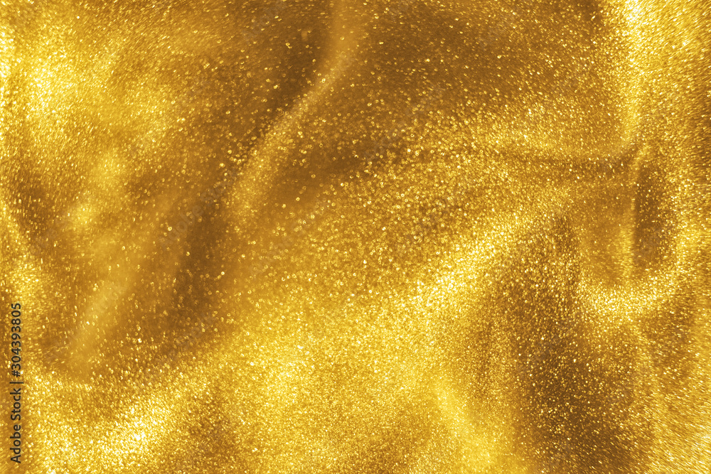 Fototapeta Abstract elegant, detailed gold glitter particles flow with shallow depth of field underwater. Holiday magic shimmering luxury background. Festive sparkles and lights. de-focused.