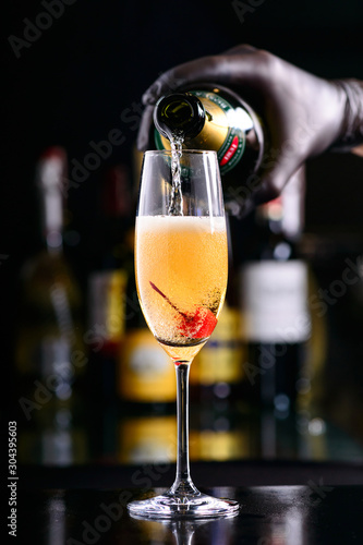 Fotografie, Tablou bartender pours bellini champagne cocktail into a glass with cherry