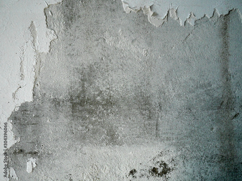 Photo of a grey wall with chapped white paint. Grunge background.