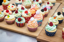 Assorted Colorful Cupcakes With Blue, Pink And Orange Frosting, Decorated With Raspberries, Marshmallow, Sprinkles And Candies.