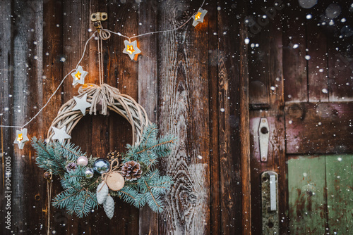 Fotografía  Christmas wreath on rustic wooden door background of blue tree.
