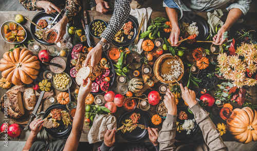 Photo sur Aluminium Pays d Europe Family celebrating Thanksgiving day. Flat-lay of eating and drinking peoples hands over Friendsgiving table with traditional Fall food, roasted turkey, candles, pumpkin pie, top view