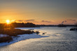Beautiful russian early winter landscape with non frozen river, snow-covered riverside and dried grass at sunset. Scenic nature background