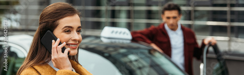 Cuadros en Lienzo Selective focus of woman talking on smartphone and taxi driver at background, pa