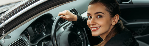 Leinwand Poster Panoramic shot of female taxi driver holding steering wheel