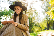 Image Of Joyful Woman Holding Diary Book While Sitting On Bench In Park
