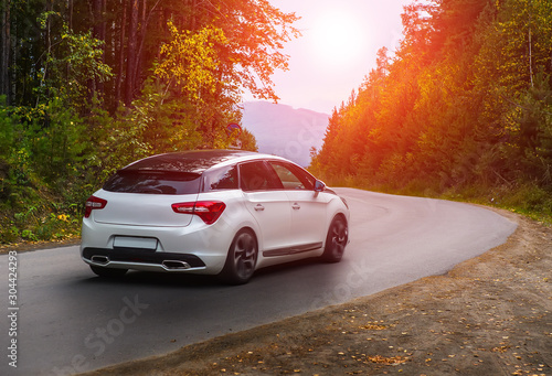 Fototapeta car rides on winding highway in an autumn forest obraz