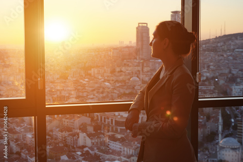 Fototapety, obrazy: Young successful businesswoman in office suit standing near the window with panoramic city view in her office in evening, sunlight. copyspace