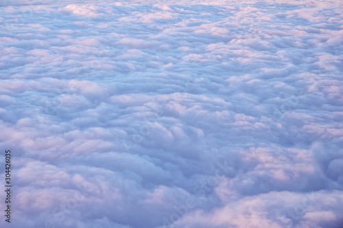 Obraz Beautiful clouds surface in sunset sky, view from plane during flight. Pink and blue cloudscape look like a snow. - fototapety do salonu