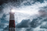 Large lighthouse with bright search light on a dark and stormy night