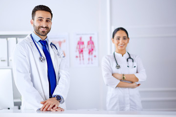 Two young smiling arab doctors standing in consultation room in hospital
