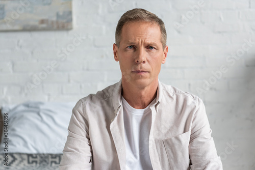 Disappointed man looking at camera in bedroom Fototapet