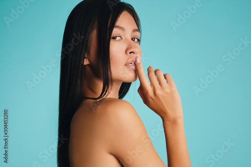 Fotografie, Obraz Attractive sexy Asian brunette girl confidently looking in camera over colorful