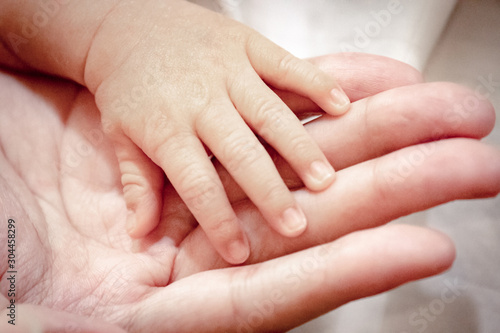 Fotografiet  Close up and selective focus at fingers of baby newborn with hand of his mother