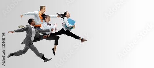 Photo Happy office workers jumping and dancing in casual clothes or suit with folders on white