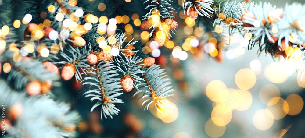 Fototapeta Christmas tree outdoor with snow, lights bokeh around, and snow falling, Christmas atmosphere.