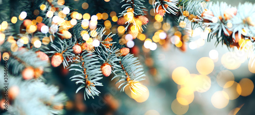 Leinwand Poster Christmas tree outdoor with snow, lights bokeh around, and snow falling, Christmas atmosphere