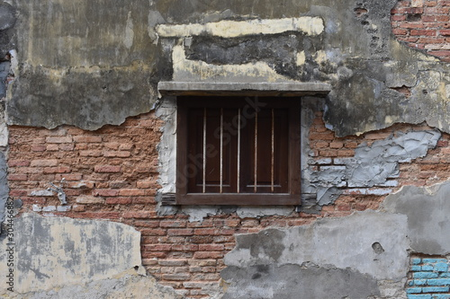 Old wooden windows with anti-theft steel on the broken old concrete wall reveals a red brick inside Wallpaper Mural