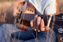 Girl Plays The Acoustic Guitar In The Field On Sunset. Fingers On Guitar Fretboard. Nature And Music. Closeup.