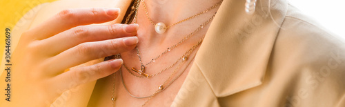 Fototapeta panoramic shot of woman touching necklace on white and yellow