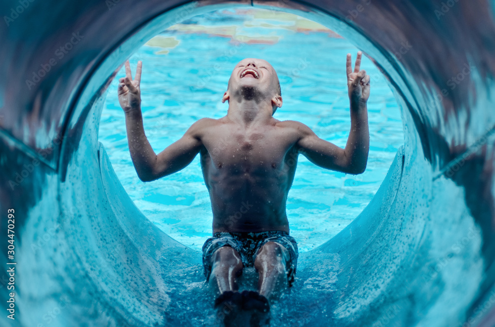 Obraz sporty boy waves his arms and starts from a blue hill down to the pool in sunny good weather on vacation fototapeta, plakat