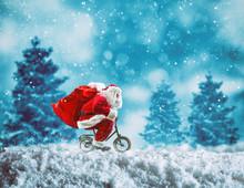 Santa Claus On A Little Bike On A Winter Landscape Under The Snow